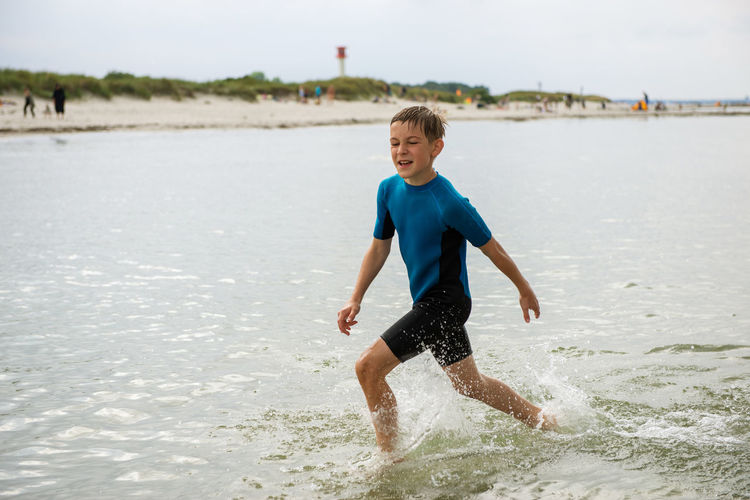 Full length of playful boy playing in sea