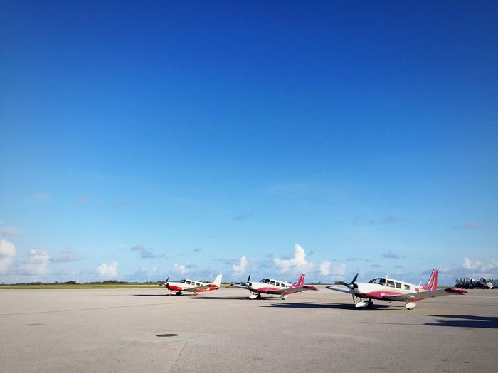 Airplane on airport runway against blue sky
