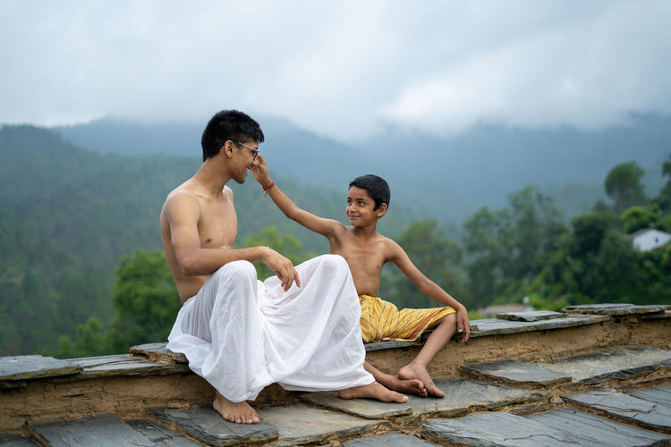 Young man with boy sitting against mountain and sky