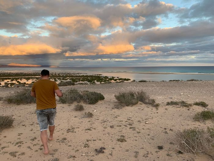 Canary Islands Fuerteventura Beach Sea Land Sky Water Cloud - Sky One Person Rear View Beauty In Nature Leisure Activity Real People Scenics - Nature Horizon Over Water Horizon Standing Sand Outdoors Full Length Nature Lifestyles
