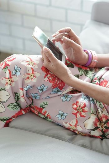 Midsection of woman using mobile phone on sofa at home