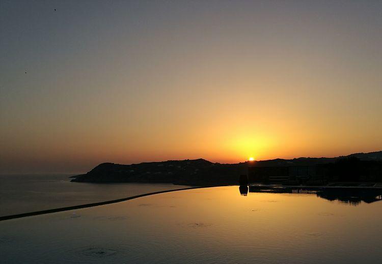 Scenic View Of Calm Sea Against Orange Sky