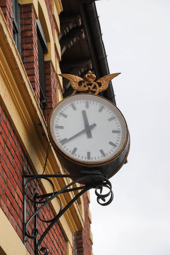 Low angle view of clock on wall against sky