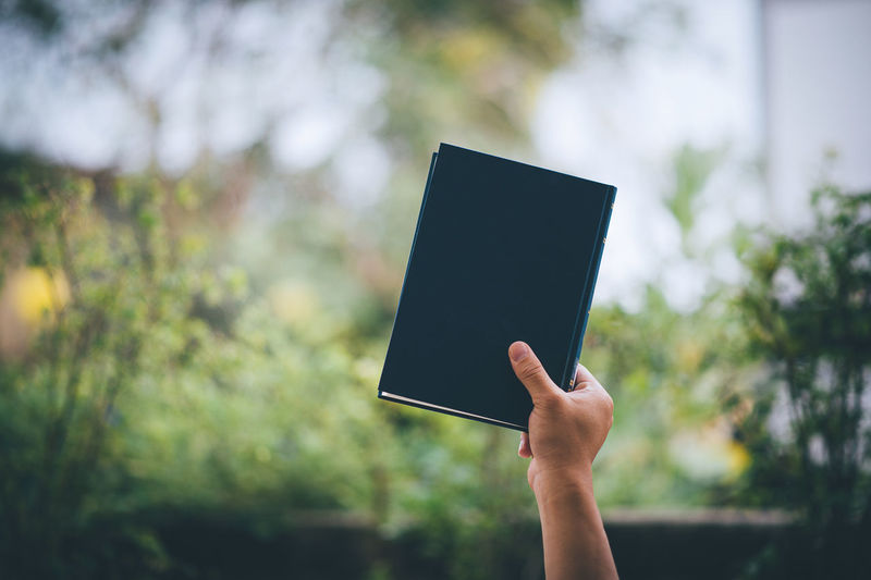Cropped hand of person holding diary against plants