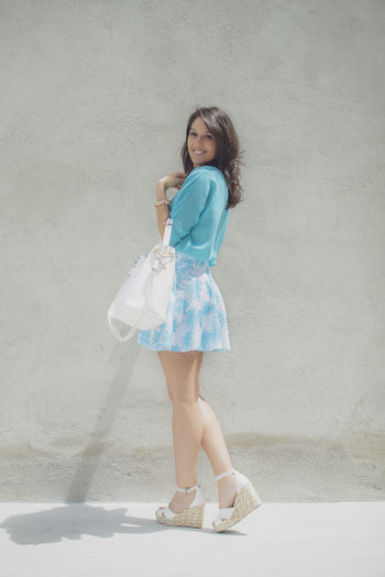 Fashion photo of a beautiful elegant young woman with a pretty palm print mini skirt and blue shirt holding handbag posing over cement background. One Person Full Length Portrait Looking At Camera Smiling Leisure Activity Real People Lifestyles Women Standing Front View Young Women Hairstyle Beautiful Woman Skirt Handbag  Blue