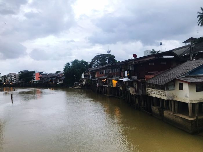 River amidst houses and buildings against sky