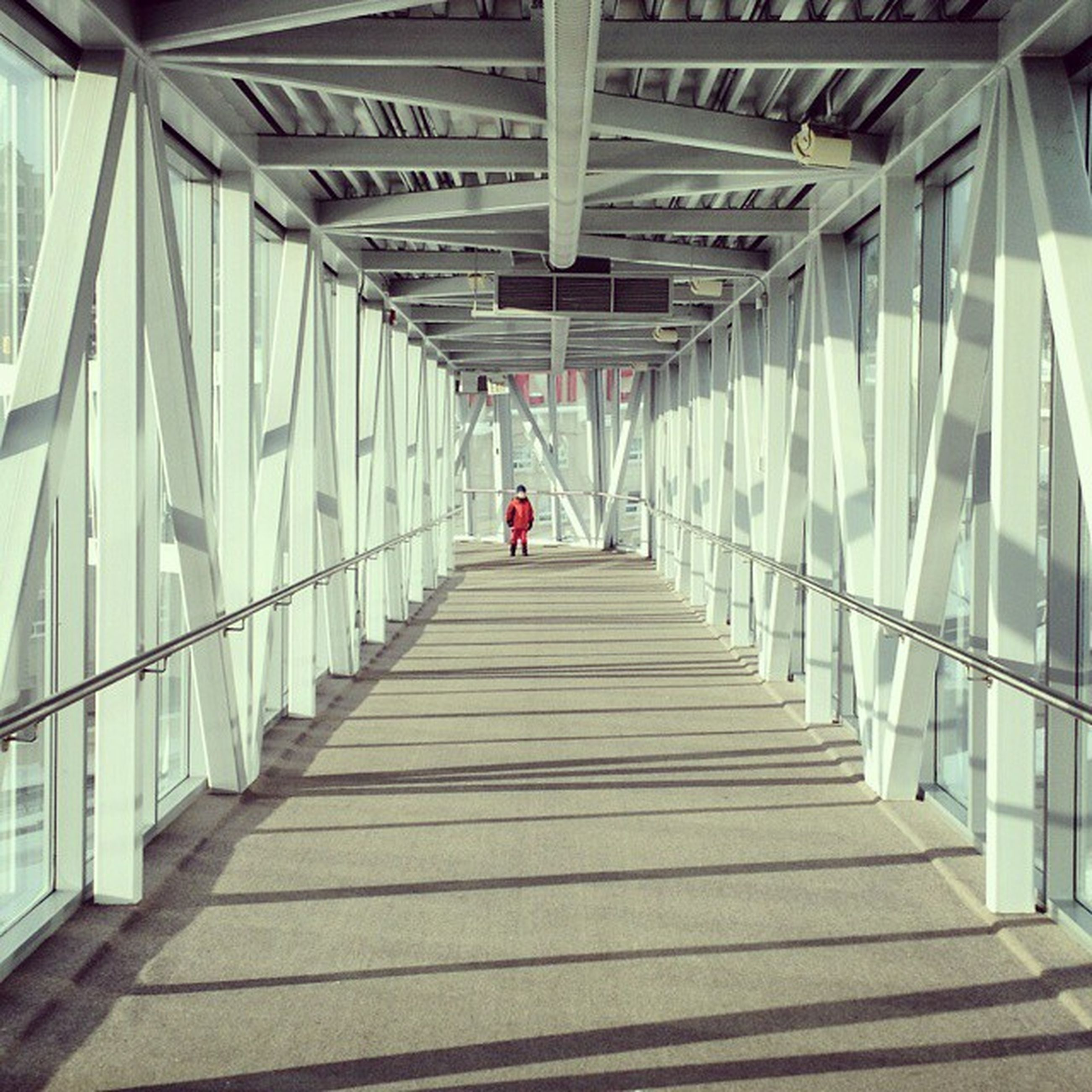 the way forward, architecture, built structure, railing, walking, men, lifestyles, rear view, indoors, diminishing perspective, full length, person, leisure activity, footbridge, vanishing point, day, steps, low angle view