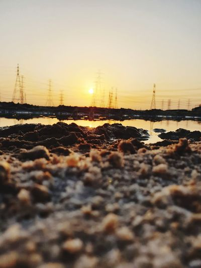 Surface level of stones on shore against sky during sunset