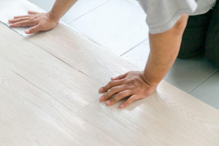 Hand installing vinyl flooring on the floor. diy, home improvement and industrial.