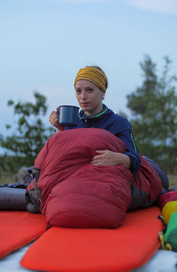 caucasian female hiker drinking beverage from cup while wild camping outdoors Backpacking Camping Coffee Expedition Hiking Hydration Nature Tea Travel Trekking Woman Activity Caucasian Clothing Cozy Day Drinking Female Front View Girl Holding Leisure Activity Lifestyles Nature One Person Outdoors Outside People Photography Themes Portrait Real People Red Relaxation Sitting Sky Sleeping Bag Technology Three Quarter Length Tree Warm Clothing Wireless Technology