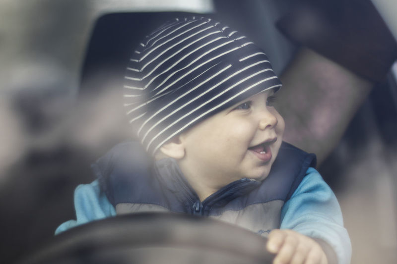 Cute smiling baby boy holding steering wheel while sitting in car