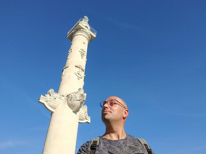 Low angle view of mid adult man looking away while standing against blue sky during sunny day