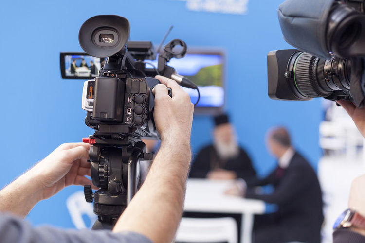 Cropped image of men filming news event with television cameras
