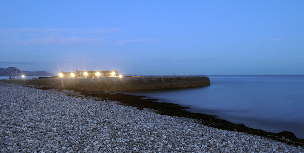 Beach Beauty In Nature English Channel Evening Sky Horizon Over Water Illuminated Jurassic Coast Lit Up Lyme Regis Night Outdoors Sea Shingle Sky Slow Shutter Speed South Coast The Cobb Water