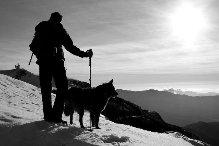 Silhouette Man With Dog Standing On Snowcapped Mountain Against Sky