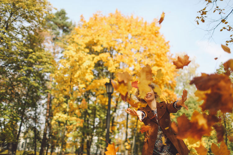 Happy Woman Throwing Dry Autumn Leaves