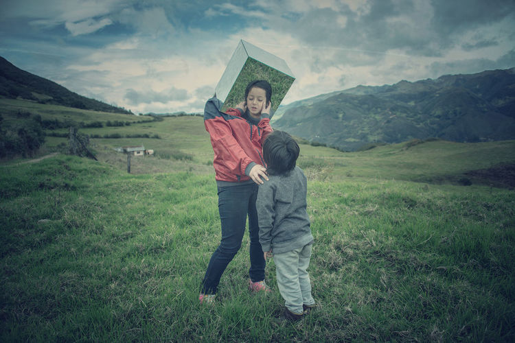 Mother wearing mirror while standing by son on grassy field