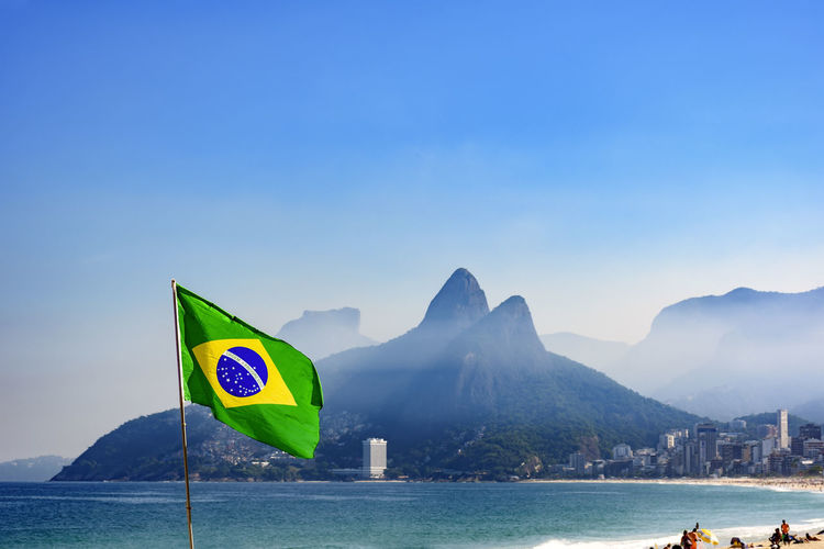 Brazilian flag at Ipanema beach in Rio de Janeiro with Two Brothers hill and Gavea stone in background Brazilian Flag Ipanema Beach National Nature Two Brothers Hill Beauty In Nature Famous Places Flag Landscape Mountain Nature Outdoor Outdoors Patriotism Scenics Sea Sky South America Summer Symbol Symbolism Tranquil Scene Tranquility Tropic Water