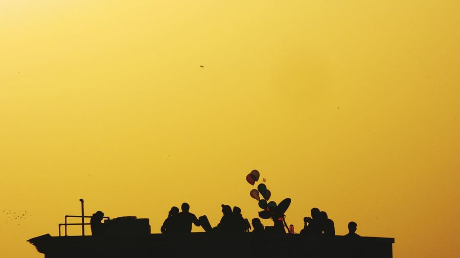 Low angle view of silhouette people enjoying at party during sunset