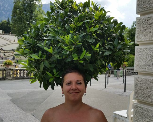 Portrait Of Smiling Woman Standing Below Tree