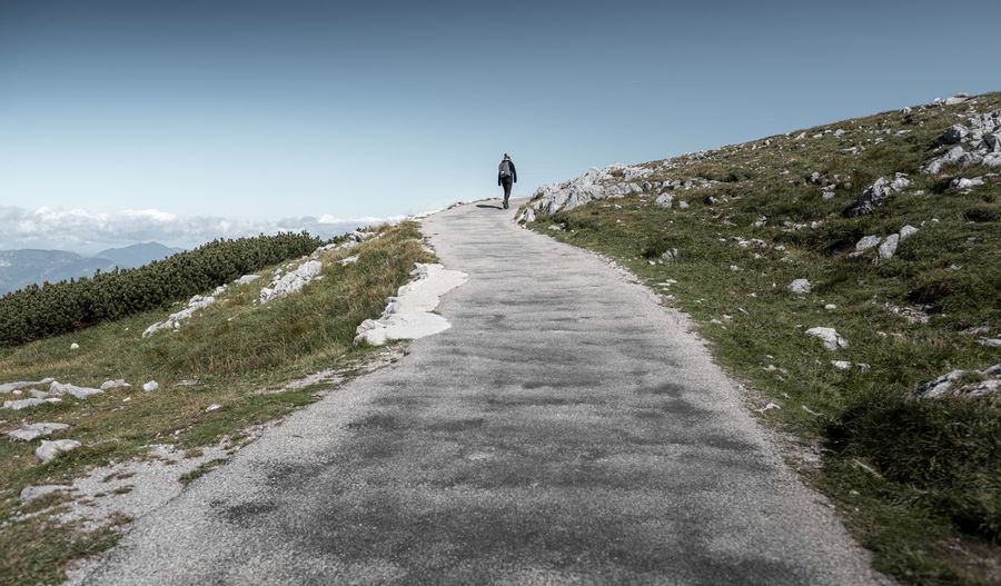 Rear view of person walking on footpath against sky