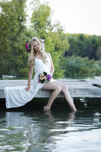Attractive blond woman sitting in pier next to the lake with nature background. Romantic bride wearing white dress and holding flower bouquet Beautiful Woman Beauty Day Fashion Flower Full Length Hair Hairstyle Lake Leisure Activity Nature One Person Outdoors Plant Real People Sitting Smiling Tree Water Waterfront Women Young Adult
