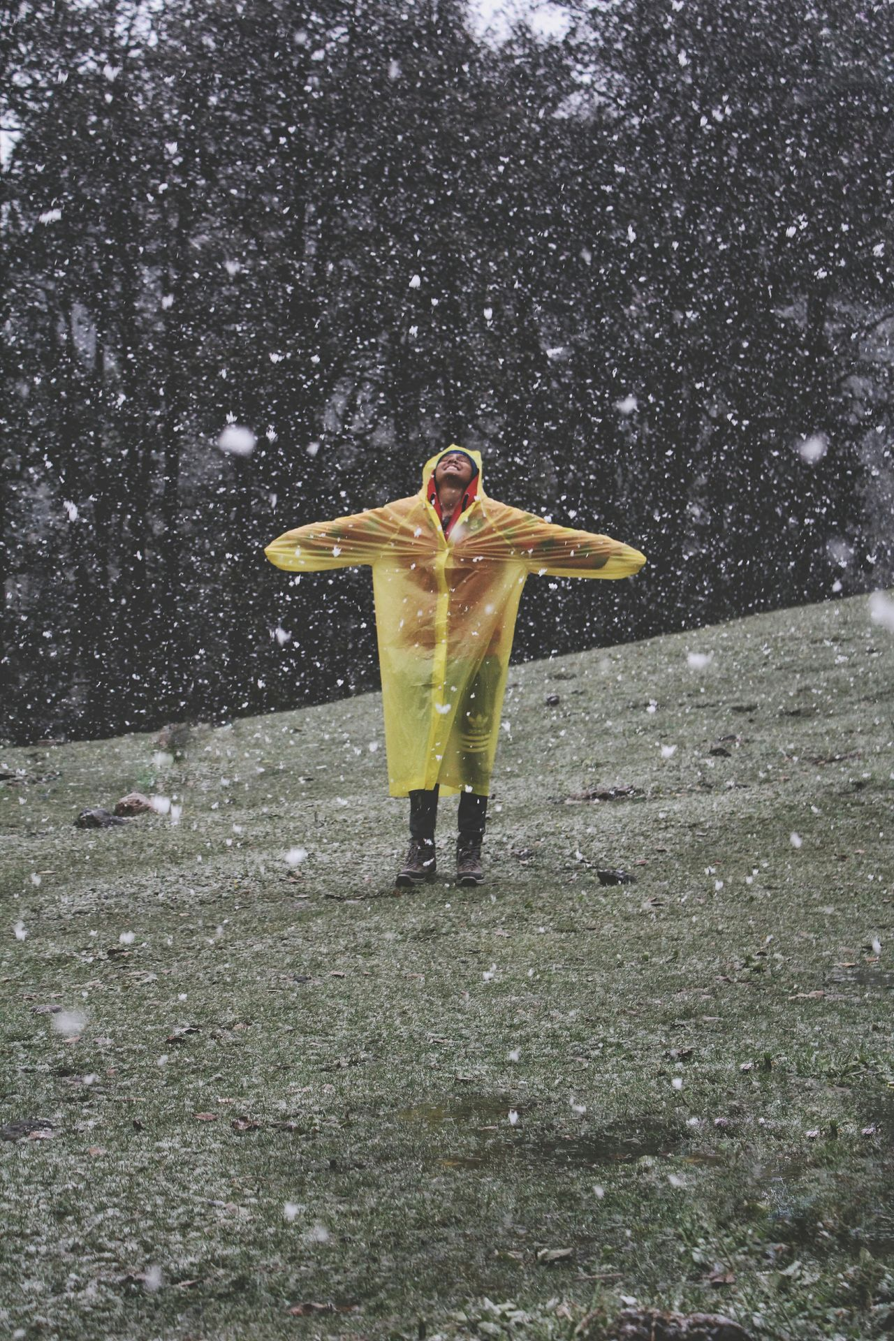 Young man with arms outstretched standing in snowfall
