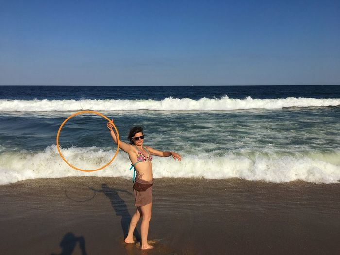 Side view of young woman with plastic hoop standing at beach against clear sky