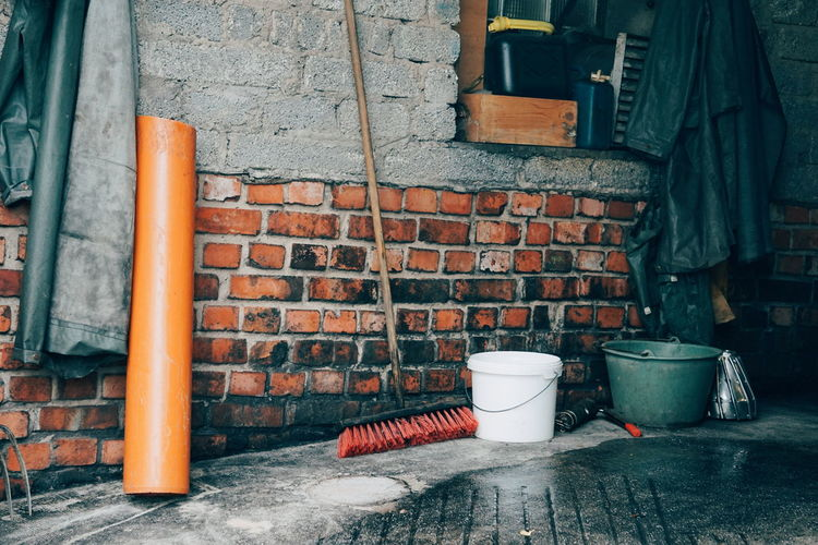 Cleaning Equipment On Footpath Against Brick Wall