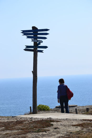 Rear view of woman standing by sign board against sea