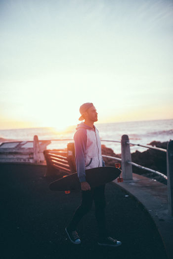 Beach Leisure Activity Lifestyles Longboard Longboards One Person People Real People Sunset Water Young Adult Young Men
