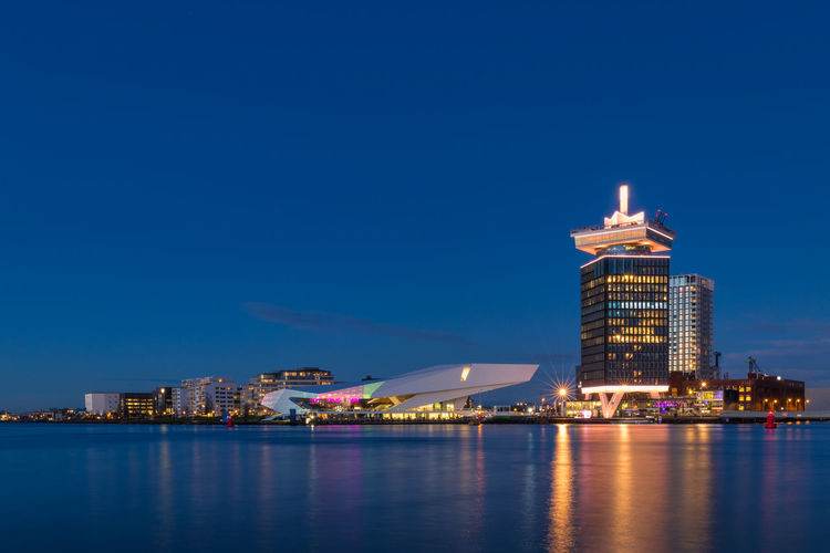 A'DAM lookout & EYE Filmmuseum Building Exterior Architecture Built Structure Water Illuminated Sky Waterfront City Building Night Reflection Nature No People Office Building Exterior Urban Skyline Travel Destinations Skyscraper Clear Sky Cityscape Outdoors Modern Amsterdam Netherlands A'DAM Lookout The EYE Filmmuseum