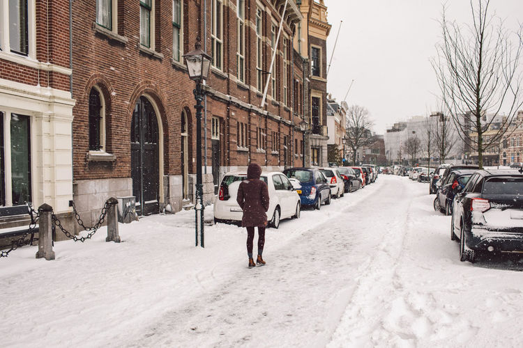 Rear view of people walking on snow covered street in city