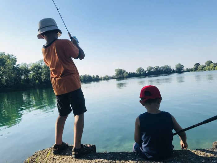 fisching Fisching Boys Water Childhood Child Real People Fishing Rod Outdoors Innocence Casual Clothing Fishing Rod Sky Nature Rear View Lifestyles Lake Leisure Activity