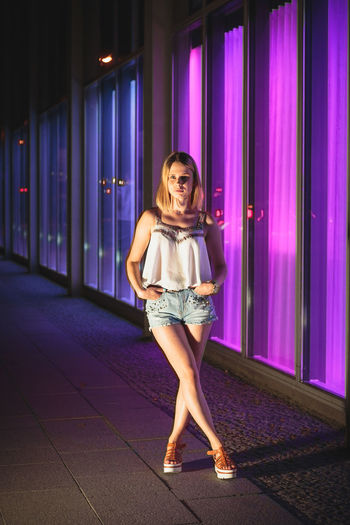 Young woman standing by illuminated windows at night