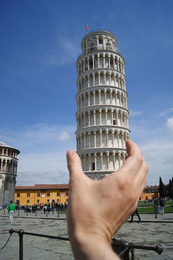 Optical Illusion Of Cropped Hand Holding Leaning Tower Of Pisa