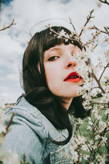 Close-up portrait of woman by plants against sky