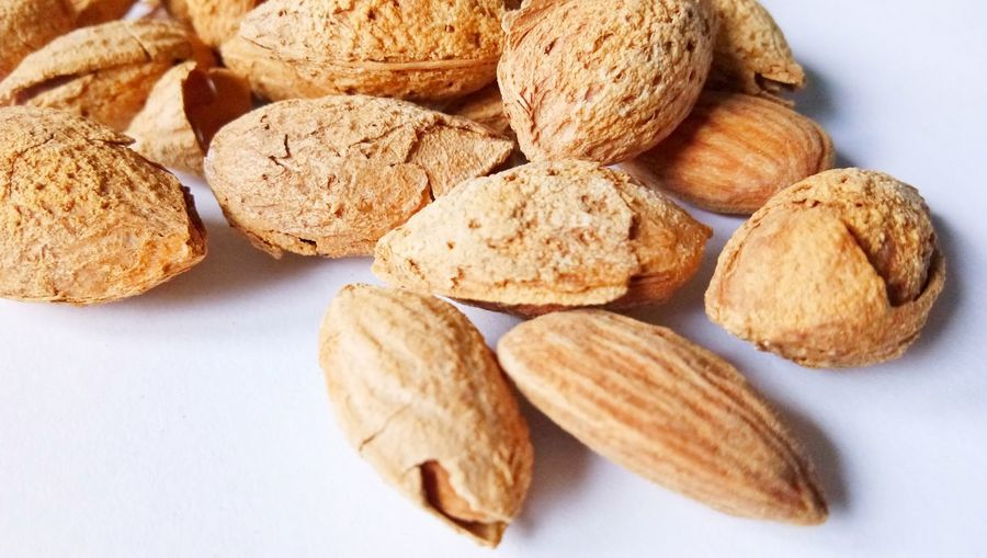 Close-Up Of Almonds Against White Background
