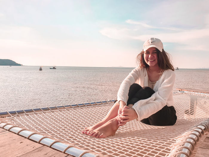 Woman sitting in sea against sky