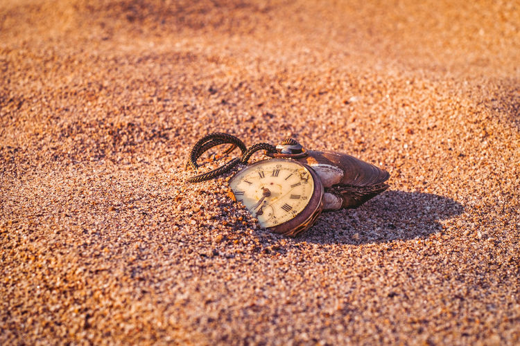 Close-up of clock on sand at beach