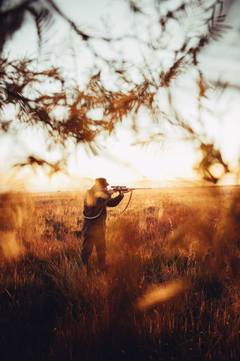 Agriculture Field Gun Hunter Hunting Leisure Activity Lifestyle Man Mature Meat Nature Outdoors People Pointing Prey Rural Scene Skill  Sniper Sunflare Sunrise Weapon