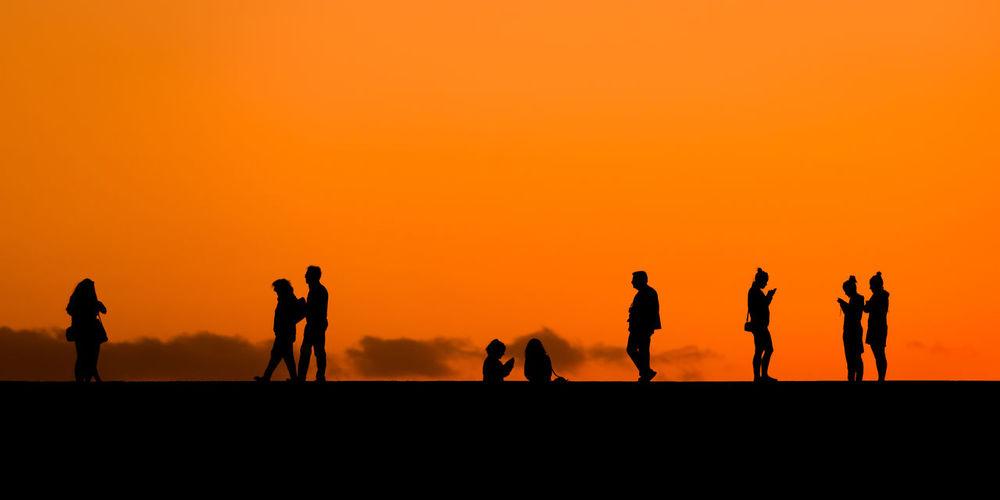 Silhouette people against orange sky