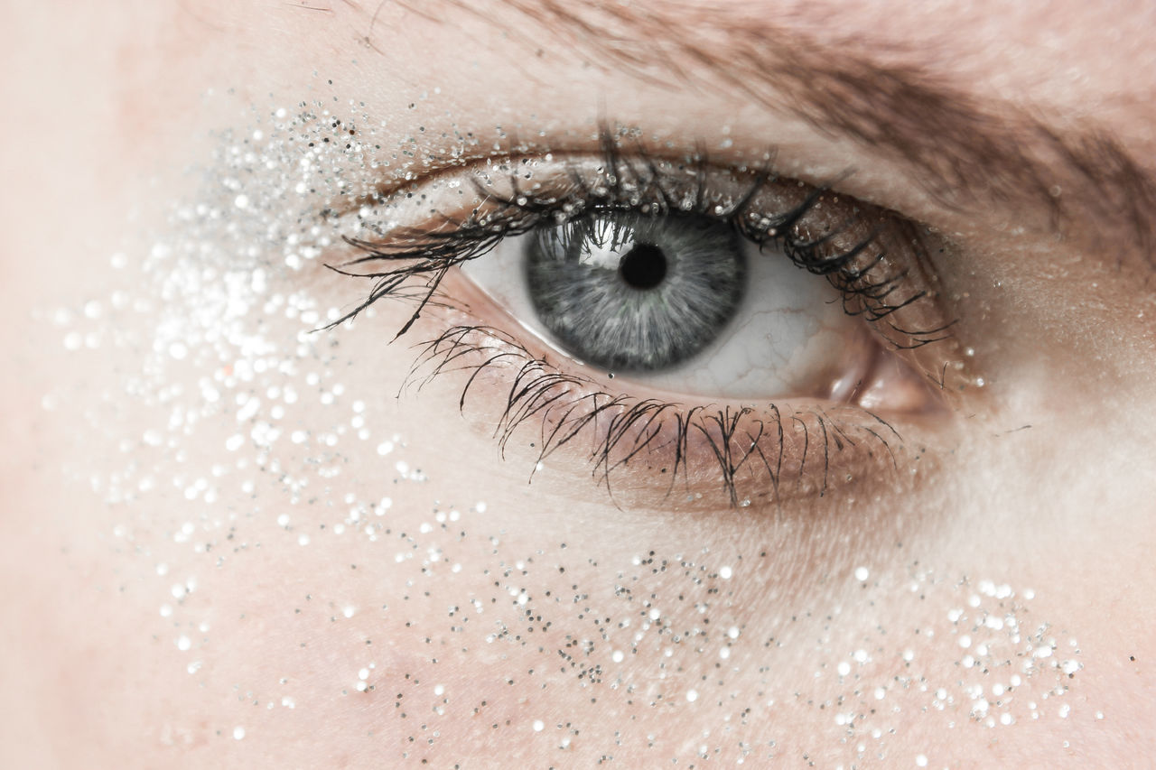 Close-up portrait of woman gray eyes with shimmer make-up