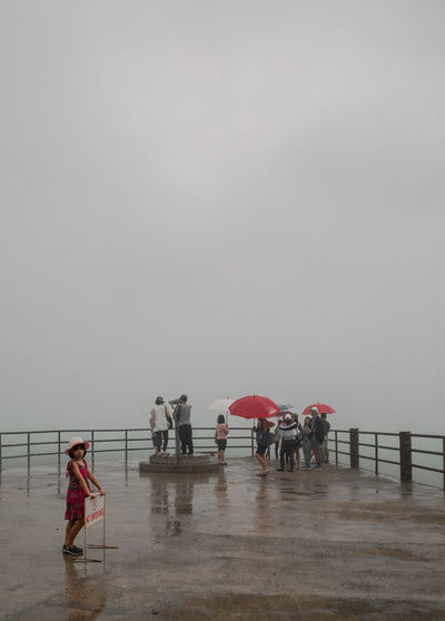 People on wet shore against sky during rainy season