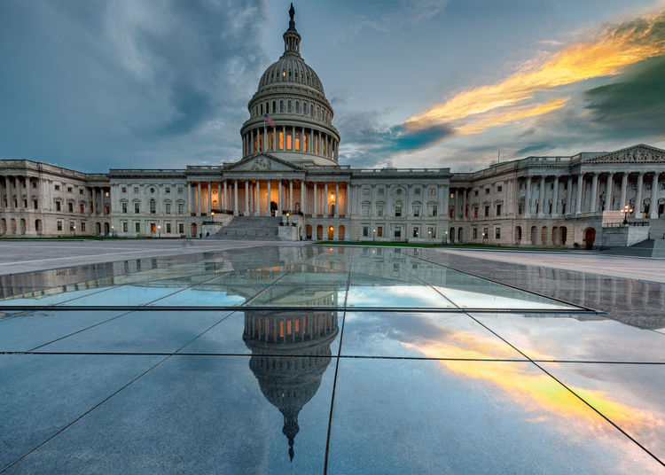 Reflection of united states capitol in water during sunset