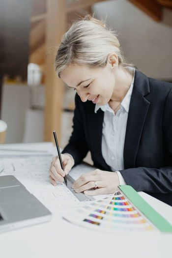Young businesswoman working on blueprint at desk in office