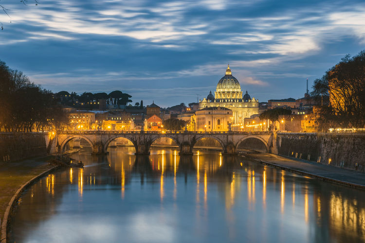 Tiber river by st peter basilica against sky at dusk