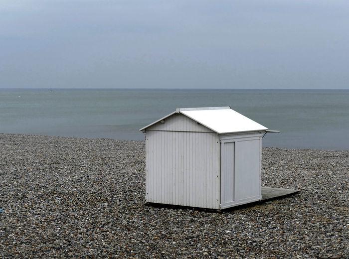 White beach hut by sea against sky