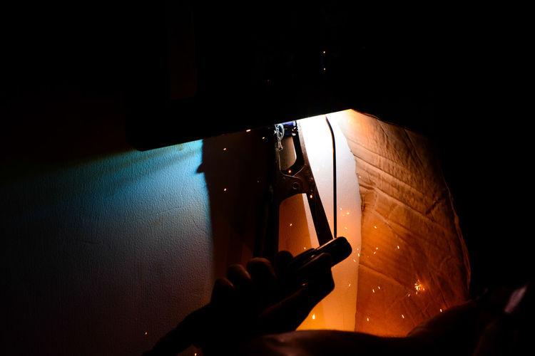 Cropped image of welder hand welding in darkroom