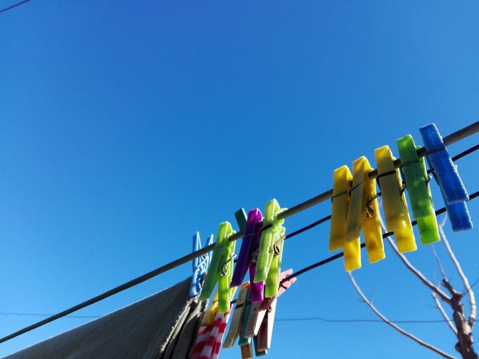 Clothespins hanging on clothesline against clear blue sky